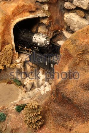 Toy Lionel O-27 Gauge Steam Engine Emerging From a Tunnel and Crossing Over a Bridge - Stock Photo