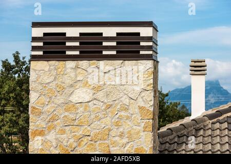 Close-up of two chimneys, one large and one small, on the roof of a residential house. Italy, Europe - Stock Photo