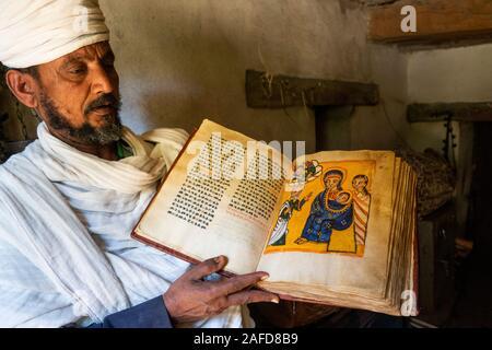 Ethiopia, Tigray, Adwa, Yeha, priest displaying Nativity page of ancient illuminated manuscript - Stock Photo