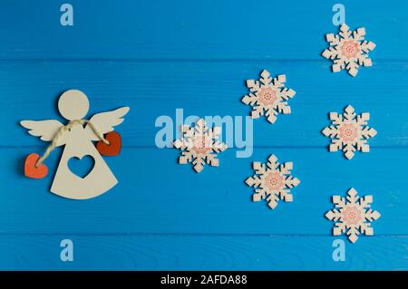 wooden Christmas figurines of angel and snowflakes are on a blue background - Stock Photo