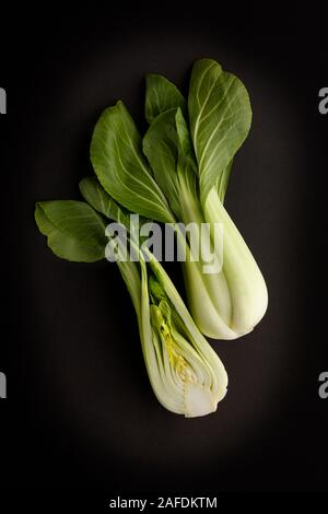 Two fresh green Bok Choy on a dark slate background, tasty ingredients in asian style cuisine, and low in calories. - Stock Photo