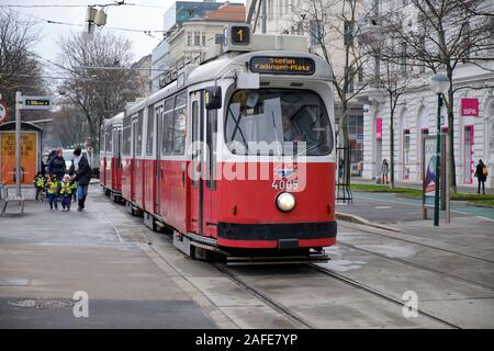 E2 type Vienna Tram at stop with driver in on school group rushing to catch it - Stock Photo