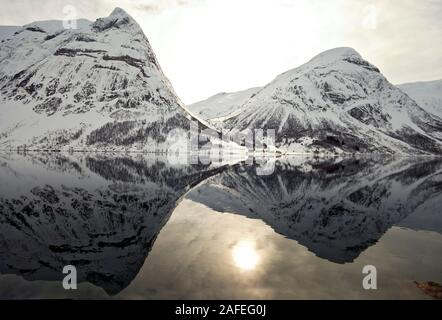 Winter sun and snowy mountains at Innvikfjord in Stryn, western Norway - Stock Photo