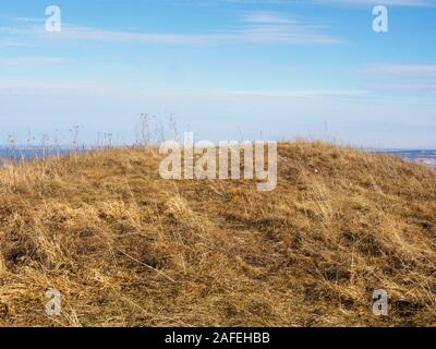 Mountain top covered with yellow grass against a blue sky. Caucasus - Stock Photo