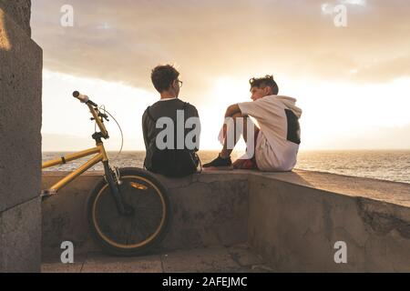 Couple of young boy talking at sunset near their bmx, sea and clouds in background. Teen sitting on a wall in a summer evening. Trendy riders enjoying - Stock Photo