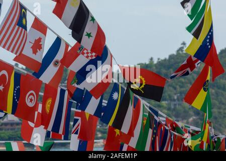 flags of the world flying in the breeze on a tropical island in thailand - Stock Photo
