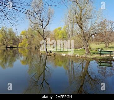 Beautiful lake and trees reflect in the water - Stock Photo