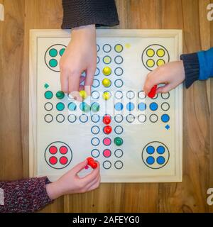 Overhead view of a family playing the board game Ludo - Stock Photo
