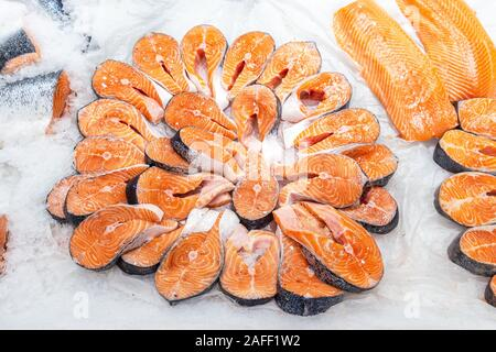 Steaks of fresh salmon on the counter in ice. Raw red fish for sale. Seafood shop - Stock Photo