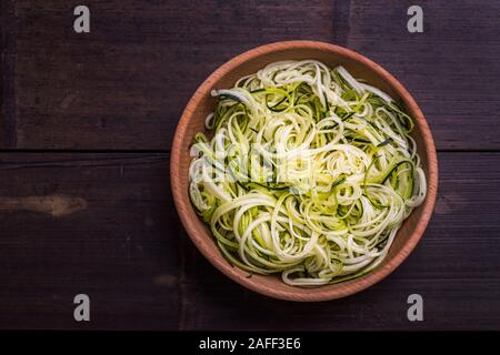 Zoodles zucchini noodles spiralized healthy  vegetable dish in a wooden bowl, on a dark bamboo table. Seen from above flat lay with copy space. - Stock Photo
