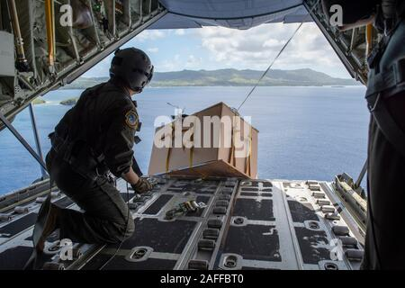U.S. Air Force Tech. Sgt. Mario Montoya air drops a low-altitude bundle containing supplies and gifts out the back of a USAF C-130 Super Hercules aircraft December 5, 2019 over Micronesia. Over the past 68-years, the U.S. Air Force Operation Christmas Drop has been providing critical supplies to 56 Micronesian islands, impacting approximately 20,000 people across an 1.8 million square nautical miles area. - Stock Photo