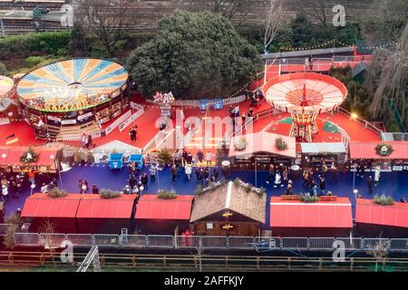 An elevated view of a small part of Edinburgh's Christmas in East Princes Street Gardens in Edinburgh city centre. The main railway lines are in the background, and the image shows fairground atrractions like the waltzers and children's chair-o-planes. Visitors are walking between the fairground rides, and in the foreground are a few of the stalls of the Christmas Market. - Stock Photo