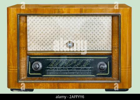 Old tube tabletop radio in wooden case, on isolated pale green background with clipping path. - Stock Photo