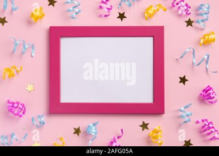Photo frame, holiday concept. Colorful serpentine and golden stars, on pink  background. Flat lay, top view, copy space. - Stock Photo