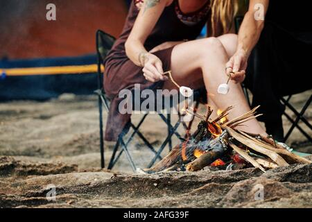 Cropped image of travelers using sticks when frying marshmallows on fire - Stock Photo