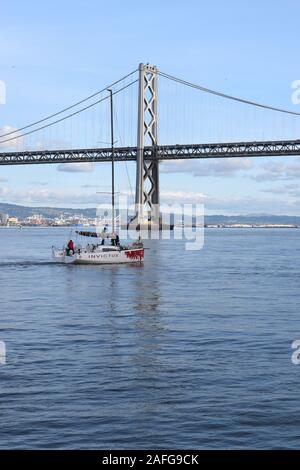 A small boat makes its way across San Francisco Bay in front of the Embarcadero piers. - Stock Photo