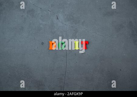 The multicolored do it word is made of wooden letters on a grey plastered wall background - Stock Photo