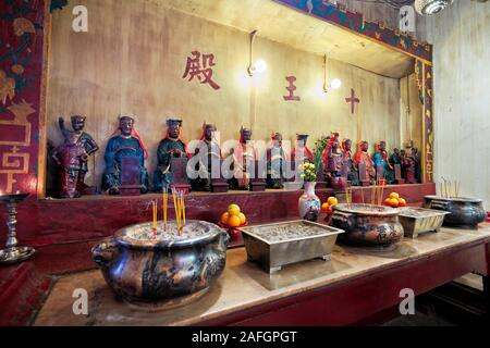 Altar with offerings in Man Mo Temple dedicated to the civil god Man Tai and the martial god Mo Tai. Sheung Wan, Hong Kong, China. - Stock Photo