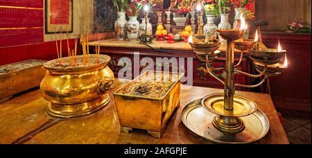 Incense urns an burning oil lamp in front of altar in Man Mo Temple. Sheung Wan, Hong Kong, China. - Stock Photo