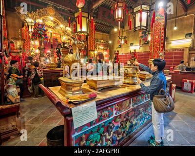 Woman puts burning incense sticks on altar in Man Mo Temple dedicated to the civil god Man Tai and the martial god Mo Tai. Sheung Wan, Hong Kong. - Stock Photo