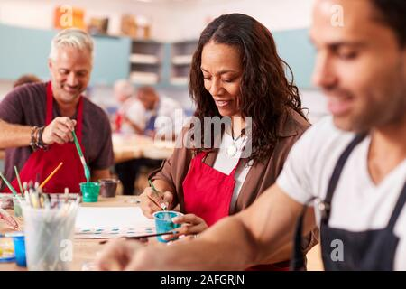 Group Of Mature Adults Attending Art Class In Community Centre - Stock Photo
