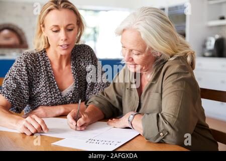 Female Friend Helping Senior Woman To Complete Last Will And Testament At Home