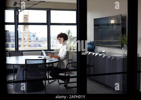 Millennial black businesswoman working alone in an office meeting room, seen through glass wall - Stock Photo