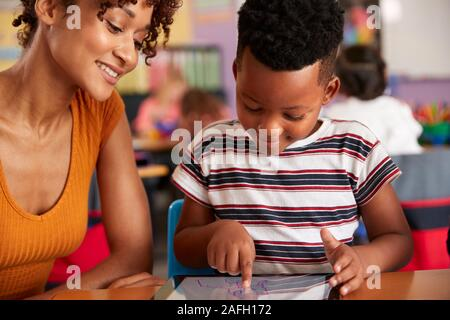 Elementary School Teacher And Male Pupil Drawing Using Digital Tablet In Classroom - Stock Photo