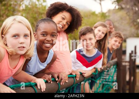 Portrait Of Children Standing On Rope Bridge With Friends In Park - Stock Photo