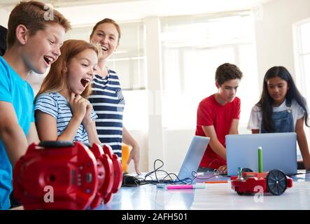 Excited Students Watching Robot Vehicle Move After Coding Lesson In Computer Programing Class - Stock Photo
