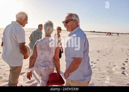 Group Of Senior Friends Walking Along Sandy Beach On Summer Group Vacation - Stock Photo