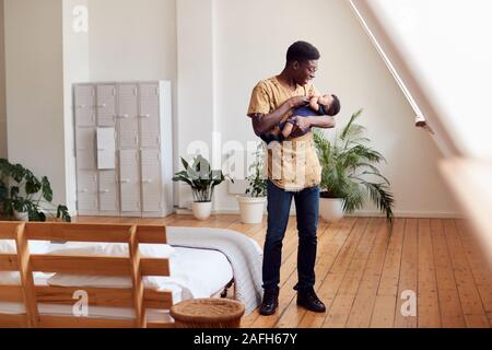 Loving Father Holding Newborn Baby At Home In Loft Apartment