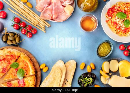Italian food background. Pizza, pasta, cheese, hams, wine, olives, pesto, capers, shot from the top, forming a frame for copy space, a flat lay - Stock Photo