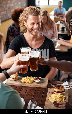 Three Young Male Friends Meeting For Drinks And Food Making A Toast In Restaurant