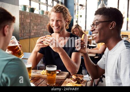 Three Young Male Friends Meeting For Drinks In Restaurant