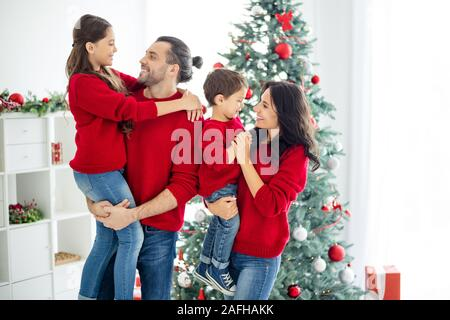 Profile side photo of big ful family charming mommy daddy schoolgirl boy enjoying christmas time x-mas holidays in house with newyear decorations - Stock Photo