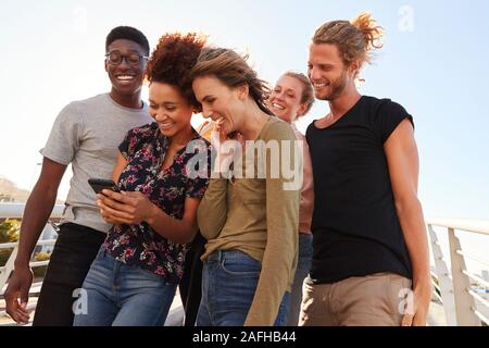 Smiling Young Friends Looking At Selfie On Outdoor Footbridge Together