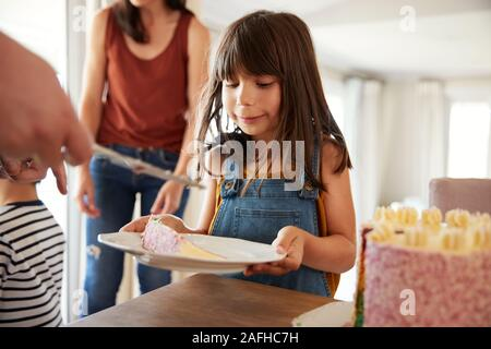 Six year old girl being served  birthday cake during a family celebration, close up - Stock Photo