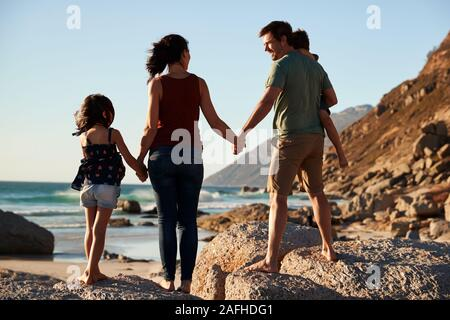 Mid adult parents and their two pre-teen children standing on beach admiring the view, full length - Stock Photo