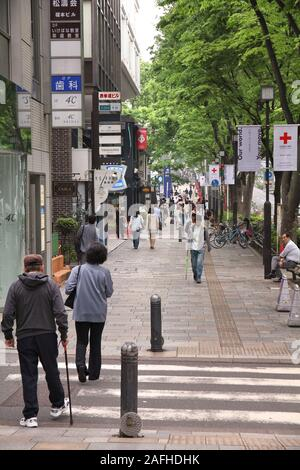 TOKYO, JAPAN - MAY 9, 2012: People shop in Omotesando district in Tokyo. Omotesando is considered one of most important shopping areas in Tokyo, the l - Stock Photo