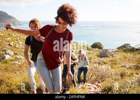 Millennial African American woman leading friends on a hike uphill by the coast, close up
