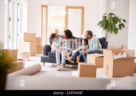 Family Taking A Break And Sitting On Sofa Celebrating Moving Into New Home Together
