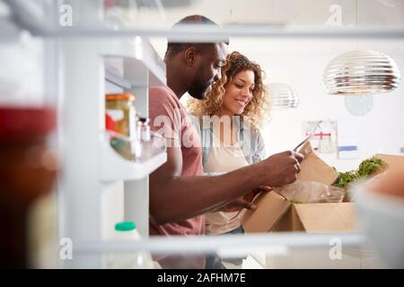 View Looking Out From Inside Of Refrigerator As Couple Unpack Online Home Food Delivery Stock Photo