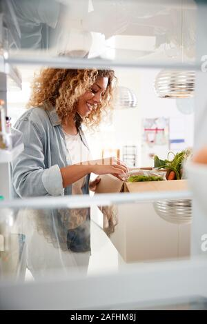 View Looking Out From Inside Of Refrigerator As Woman Unpacks Online Home Food Delivery Stock Photo