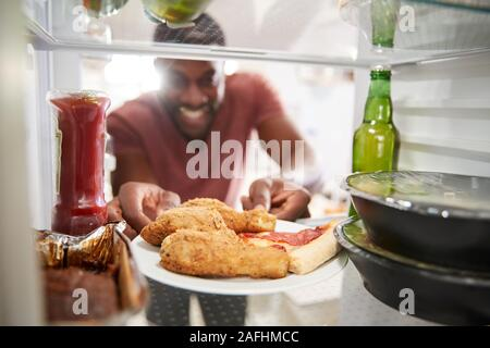 View Looking Out From Inside Of Refrigerator Filled With Unhealthy Takeaway Food As Man Opens Door Stock Photo