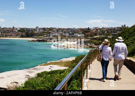 Sydney walking; a couple on the sydney coast, on the Bondi to Clovelly beach walk in spring, arriving at Tamarama and Bronte beaches, Sydney Australia - Stock Photo