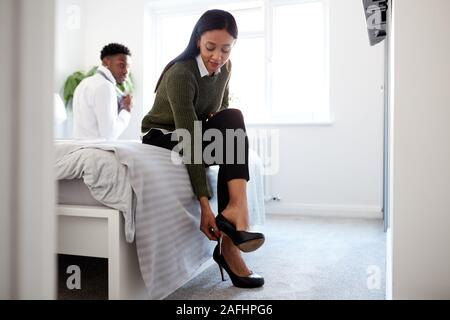Business Couple In Bedroom Getting Ready For Work Businesswoman At Home Putting On Shoes - Stock Photo