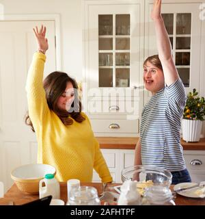 Young Downs Syndrome Couple Having Fun Baking In Kitchen At Home - Stock Photo