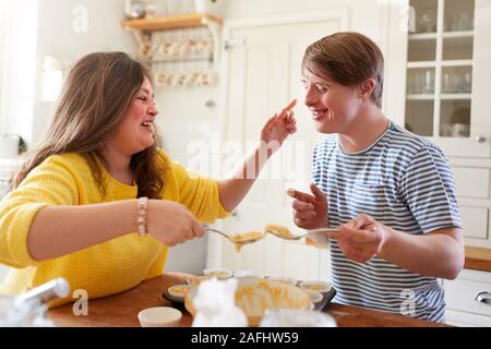 Young Downs Syndrome Couple Having Fun Baking Cupcakes In Kitchen At Home - Stock Photo