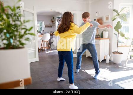 Young Downs Syndrome Couple Having Fun Dancing At Home Together - Stock Photo